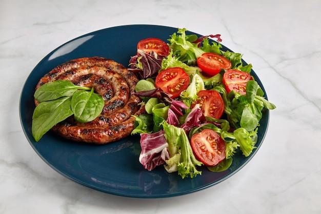 大理石のテーブルの青いプレートにトマトとハーブを添えたスパイラルグリルソーセージ