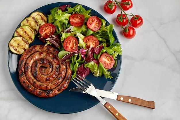 大理石のテーブルにカトラリーを添えた青いプレートにトマトとハーブを添えたスパイラルグリルソーセージ