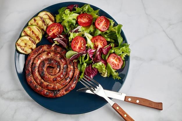 Спиральная колбаса на гриле с помидорами и зеленью на синей тарелке