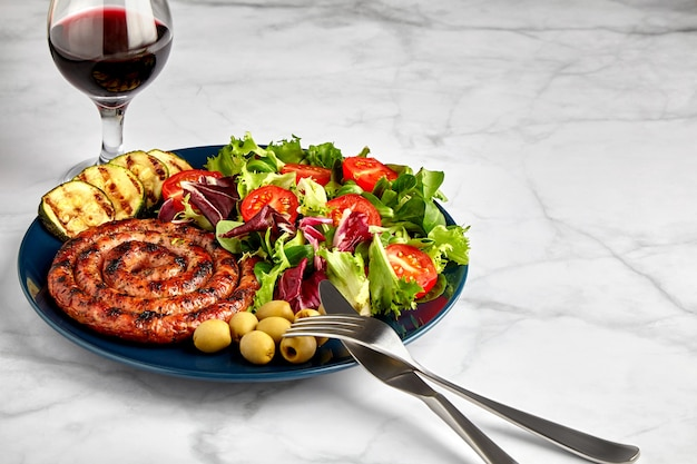 Spiral grilled sausage with vegetables and herbs on a plate with cutlery and a glass of red wine on a marble table