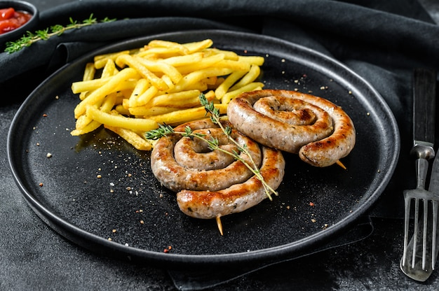 Spiral grilled sausages with a side dish of french fries. black background.