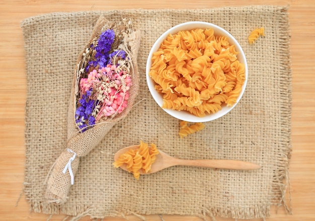 Spiral macaroni in bowl on sack decoration with dry flower bush against wood background