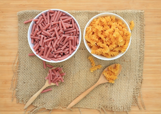 Spiral macaroni and red pasta in white bowl on sack against wood.