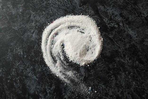 Spiral made of washing powder on black smokey table