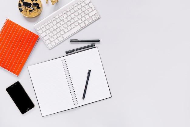 Спиральный ноутбук и ручка с мобильного телефона и клавиатуры на белом фоне