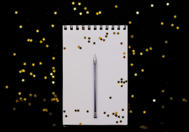Spiral notebook, realistic mockup  golden stars confetti.horizontal top view.
