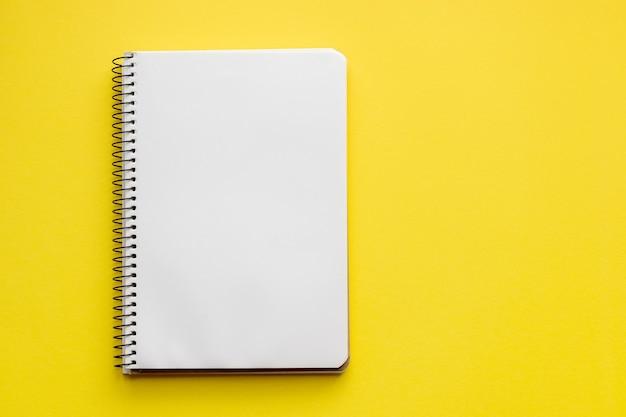 Спиральный блокнот с пустыми пустыми листами на желтой поверхности