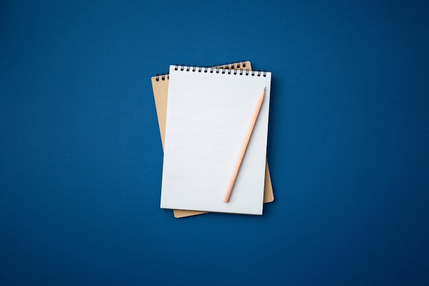 Spiral notebook with a pencil on blue wall. office table top view concept.
