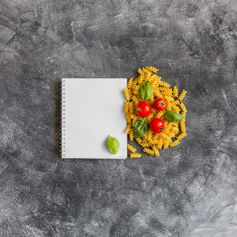 Spiral notebook with raw fusilli; tomatoes and basil leaves