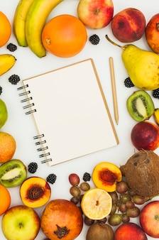 多くの色とりどりの果物に囲まれたスパイラルメモ帳と鉛筆