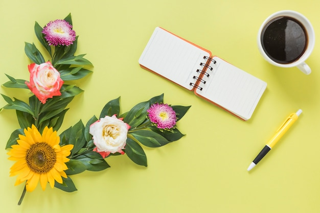 Spiral notepad; black tea; pen and flowers on colored background