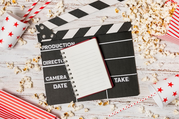 Spiral notepad; clapperboard; drinking straw and popcorns on wooden desk