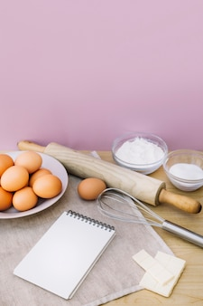 Spiral notepad; eggs; whisk; rolling pin; sugar; white chocolate and flour on desk