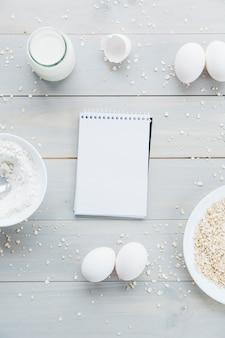 スパイラルメモ帳。オーツ麦;卵;小麦粉、牛乳、木製、背景
