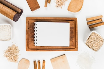 Spiral notepad on wooden tray surrounded with rice and cinnamon sticks