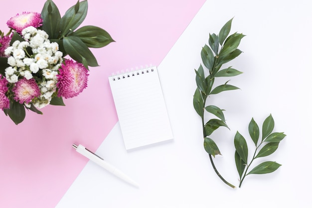 나선형 메모장; 펜; 이중 배경에 나뭇잎과 꽃의 무리