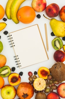 Spiral notepad and pencil surrounded with many colorful fruits