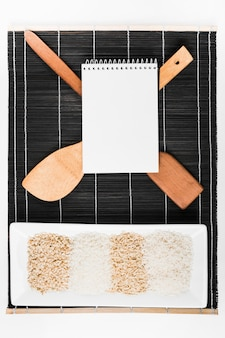 Spiral notepad over the spatula and tray of uncooked rice on black placemat