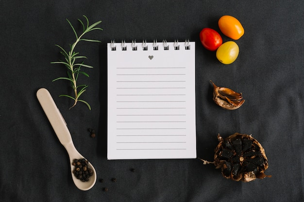 Spiral notepad surrounded with rosemary; cherry tomatoes; black pepper and garlic