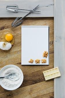 Спиральный блокнот; грецкий орех; шоколад; мука; яйцо и венчик на деревянной поверхности