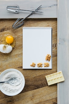Spiral notepad; walnut; chocolate; flour; egg and whisk on wooden surface