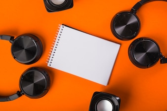 Spiral notepad with black headphones and speakers over an orange background