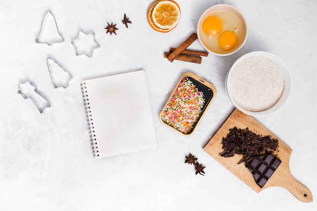 Spiral notepad with colorful sprinkles; pastry cutter; star anise; cinnamon; dried citrus; egg yolk and chocolate bar on white backdrop