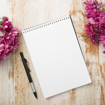 Spiral notepad with pen and pink flowers on wooden textured background