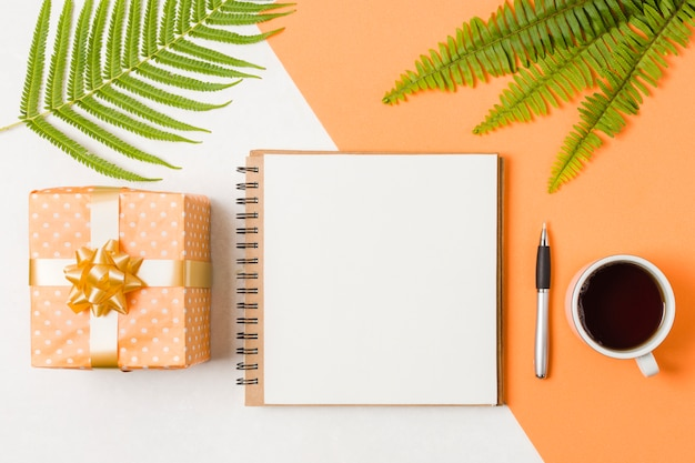 Spiral notepad with pen; orange gift box and black tea near green leaves over dual surface