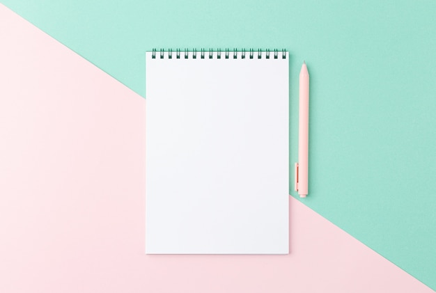 Spiral notepad with pen on two colour background