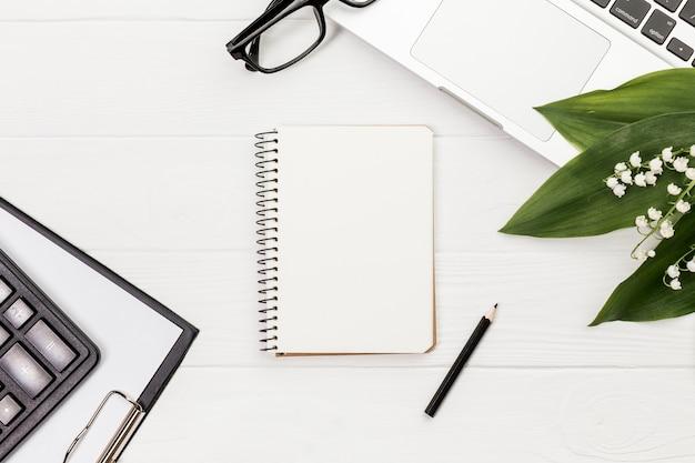 鉛筆、電卓、クリップボード、眼鏡、白い机の上のノートパソコンとスパイラルメモ帳