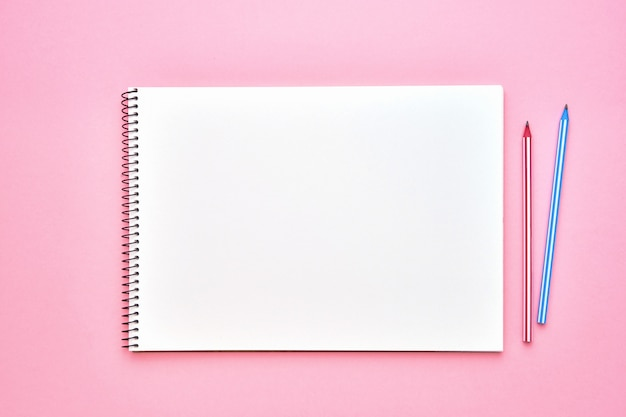 Spiral notepad with pencils on pastel pink. back to school concept. copy space, top view.