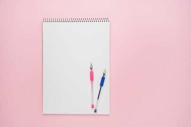 디자인을위한 모형으로 펜이있는 나선형 메모장. 파스텔 핑크 배경에 노트북입니다. 다시 학교 개념. 공간 복사