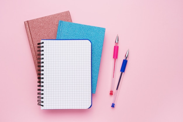 Spiral notepad with pens as mockup for your design on pink. back to school concept. copy space, top view.