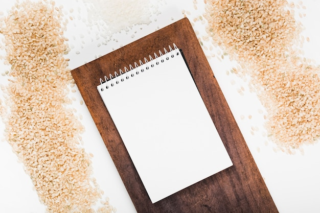 Spiral notepad on wooden tray with variety of rice on white background