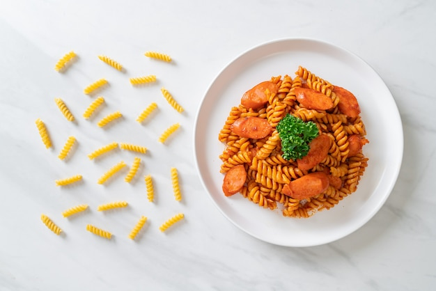토마토 소스와 소시지를 곁들인 나선형 또는 나선형 파스타. 이탈리아 음식 스타일