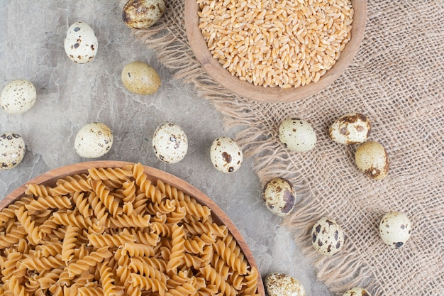 Spiral pastas in a wooden platter with wheat grains and quail eggs.