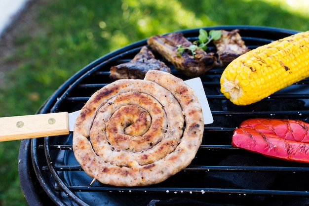 Spiral sausages, vegetables and meat on grill