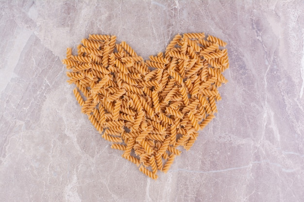 Spiral shape pastas in heart shape on the marble.