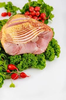 Spiral sliced hickory smoked ham with fresh kale and radish.