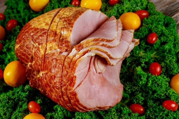 Spiral sliced hickory smoked ham with fresh lemon, kale and tomatoes. holiday meal.
