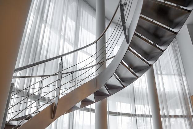 Винтовая лестница в особняке на фоне широкого окна, прикрытого белыми шторами