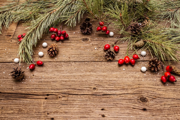 Spirit christmas on wooden table. fresh dog-rose berries, ball candies, pine branches and cones, artificial snow. nature decorations, vintage wooden boards