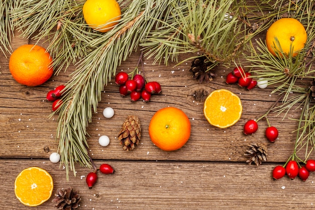 Spirit christmas on wooden table. fresh mandarins, dog-rose berries, candies, pine branches and cones, artificial snow