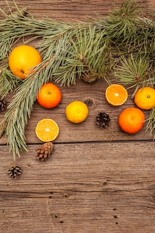 Spirit christmas on wooden table. fresh oranges, tangerines, pine branches and cones. nature decorations, vintage wooden boards