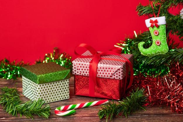 精神的なクリスマス。クリスマスツリーの横にある木製のテーブルに置かれた明るいお祝いパッケージに包まれたギフトのペア。クリスマス。