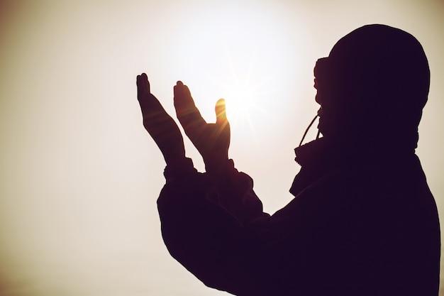 흐리게 아름 다운 석양과 태양 빛 위에 영적기도 손