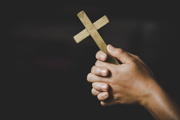 영성과 종교, 종교 개념에 여자 십자가 상징을 들고 하나님 께기도 손. 수녀는 그의 손에 십자가를 잡았다.