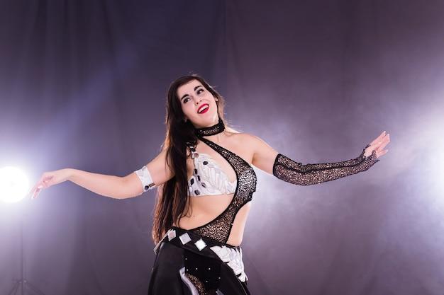 Духовный танец. красивая сексуальная женщина с роскошным глянцевым восточным макияжем танцует племенной фьюжн