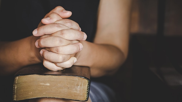 Spirituality and religion, hands folded in prayer on a holy bible in church
